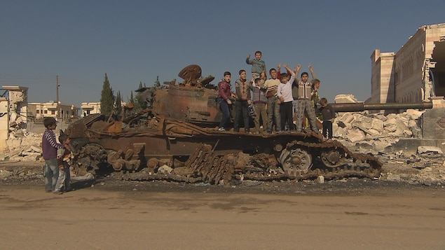 Des enfants sur la carcasse d'un char d'assaut dans une zone de guerre.
