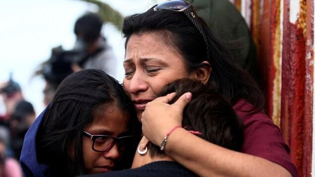 Des parents séparés de leurs enfants par les services d'immigration s'enlacent à la frontière.