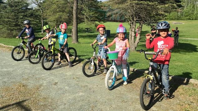 Six enfants, cinq garçons et une fille, à cheval sur leur bicyclette. Ils portent tous un casque. Ils sont dans un parc sur un sol rocheux. Ils sont arrêtés, les pieds au sol, et regardent la caméra.