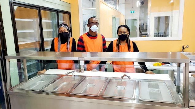3 personnes masquées dans un restaurant derrière de l'équipement de cuisine.