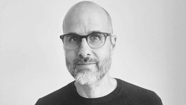 Une photo en noir et blanc d'Eric Fillion qui porte des lunettes et la barbe.
