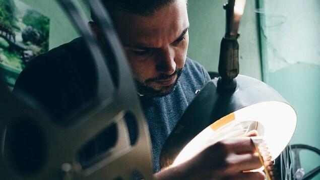 Le programmateur du cinéma Revue, Éric Veillette regarde une bobine de film sous une lumière.