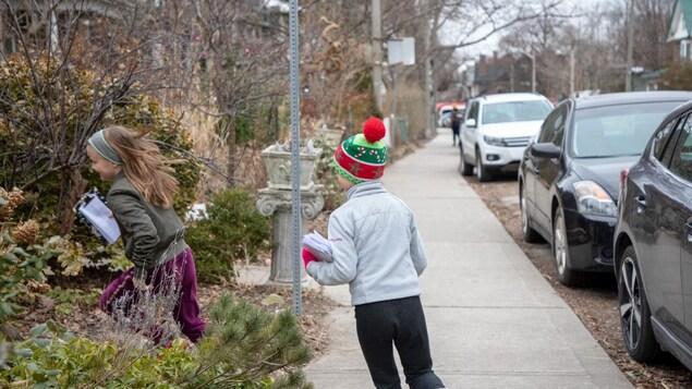 Des jeunes distribuent des lettres dans un quartier résidentiel à l'ouest du centre-ville de Toronto.