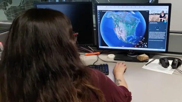 Une jeune femme assise devant un ordinateur, présentant une image de la planète terre.