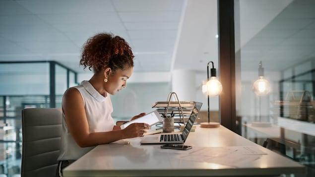 Une femme travaille sur une tablette informatique; un ordinateur est posé sur son bureau.