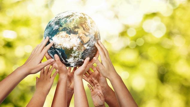 Des mains d'enfants tiennent à bout de bras une petite planète Terre.