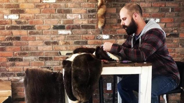 Le trappeur est assis à une table en train de coudre des peaux de castor.