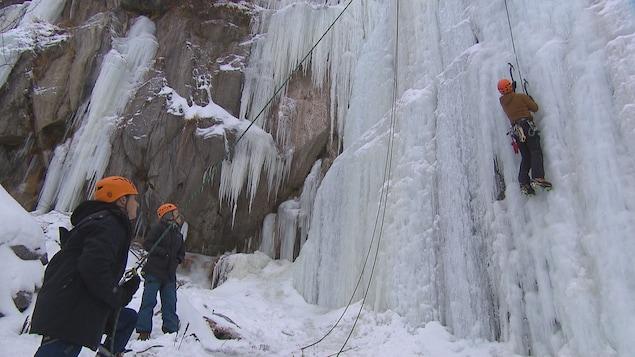 Un homme qui grimpe une paroi de glace.
