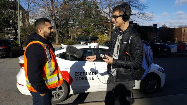 Un homme portant un dossard orange parle dans un micro tenu par un autre homme, devant une voiture sur laquelle on peut lire « Escouade mobilité ».