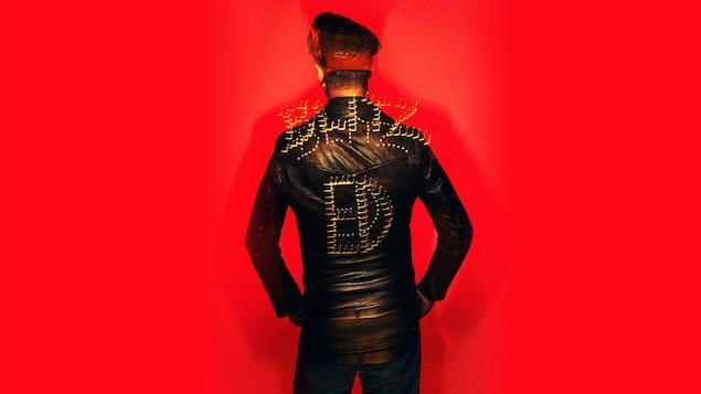 Le chanteur Étienne Daho, de dos, porte un blouson de cuir sur lequel il est inscrit « ED ».