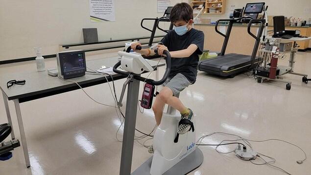 Un jeune se trouve sur un équipement de sport dans un laboratoire de l'Université de la Saskatchewan.