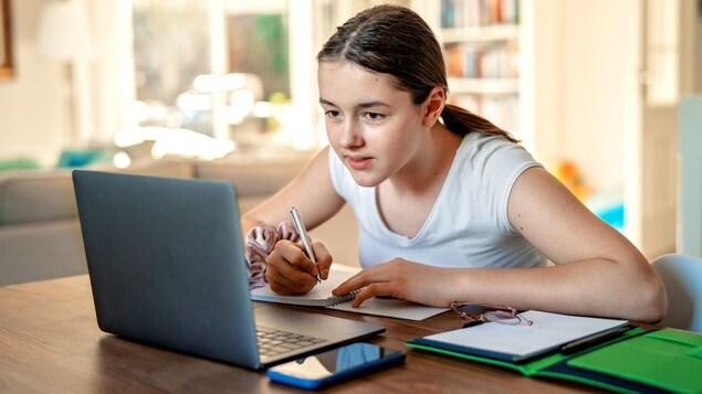 Une étudiante étudie en prenant des notes devant son ordinateur.