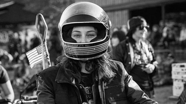 Photo en noir en blanc de la jeune femme, un casque de moto sur la tête et portant une veste de cuir.