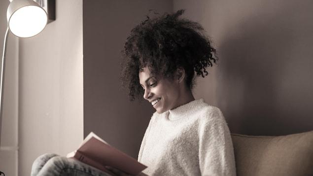 Une jeune femme lit un livre.