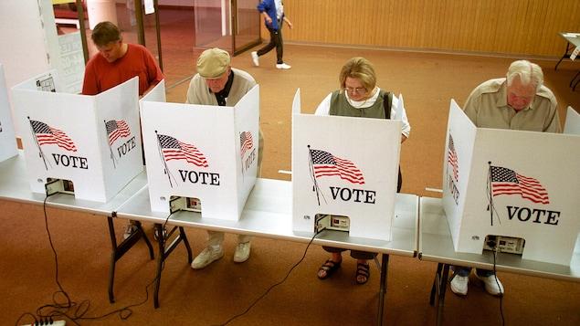 Dans un bureau de vote, quatre citoyens votent à l'élection présidentielle américaine.