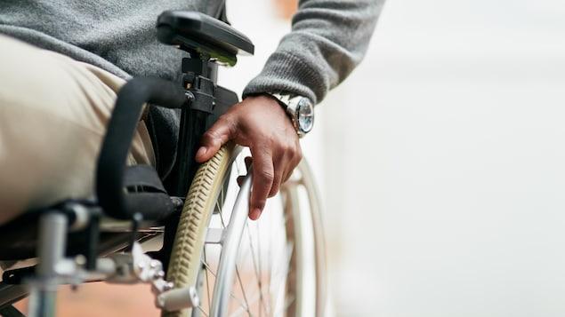 Un homme en fauteuil roulant a une main posée sur une roue.
