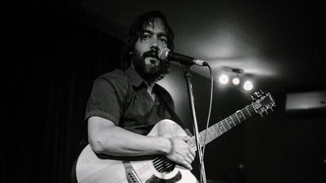 Photo en noir et blanc d'un homme sur un scène devant un micro et tenant un guitare.