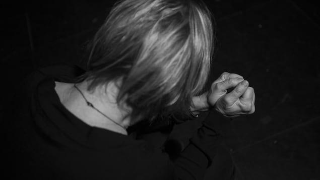 Dans un fond sombre, une femme vue de dos semble faire une prière, sauf qu'elle a les poings serrés.