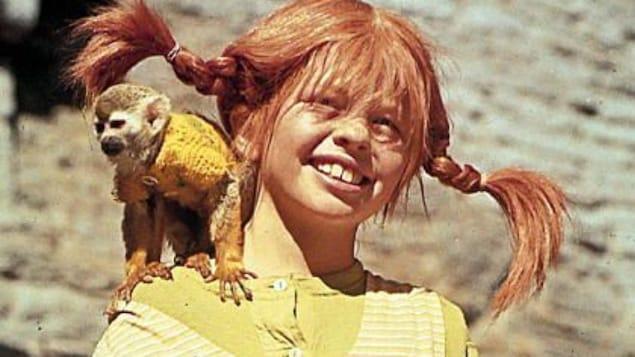 Une jeune fille rousse porte des tresses et a un petit singe sur l'épaule.