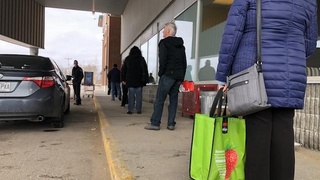 Des gens font la file devant un commerce de Baie-Comeau.