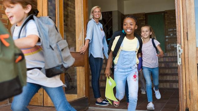 Des élèves sortent en courant d'un immeuble qui semble être une école. Une femme aux cheveux blonds souriante tient la porte ouverte.