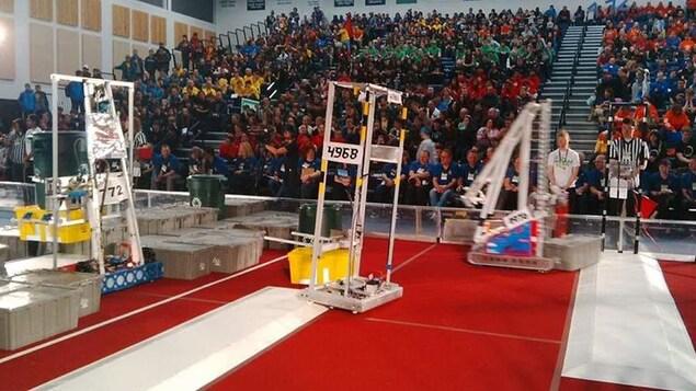 Des robots dans une aréna avec du public sur les gradins.