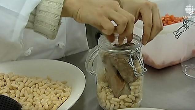 Mise en pot de charcuterie de canard pour constituer un cassoulet.
