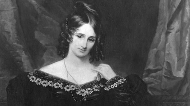 Mary Shelley, une plume à la main, semble écrire sur une feuille alors que plusieurs livres sont éparpillés sur la table.