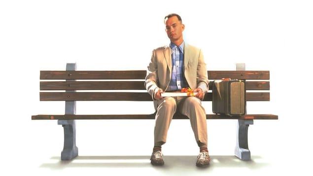 Un homme est assis sur un banc public avec une boite de chocolat sur les genoux.