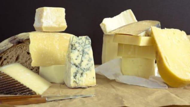 Différentes sortes de fromages avec un couteau et du pain.