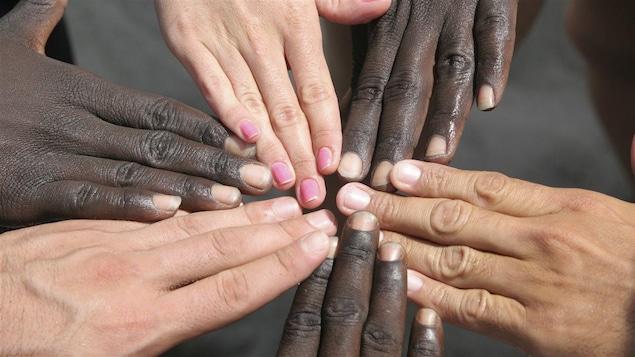 Des mains de différentes couleurs se joignent.