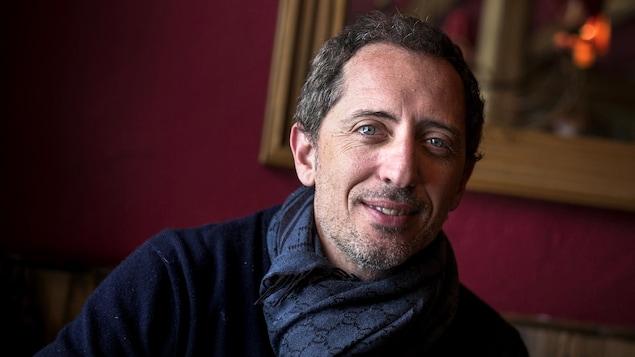 L'humoriste Gad Elmaleh, portant un foulard, dans un salon rouge.