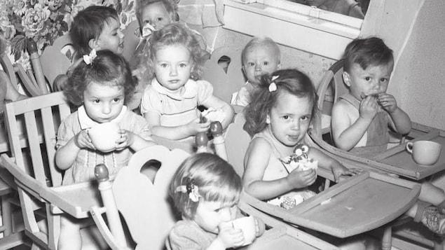 Huit enfants qui mangent assis dans des chaises hautes.