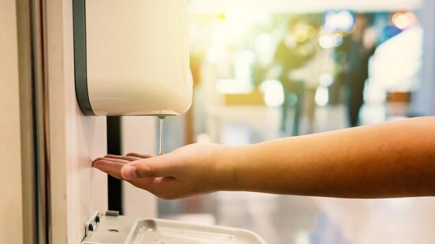 Une main tendue reçoit du gel d'un distributeur automatique.