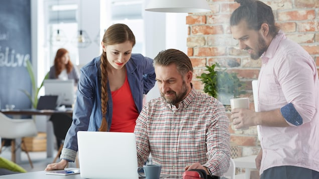 Une jeune femme, un jeune homme et un homme d'âge mûr devant un ordinateur portable.