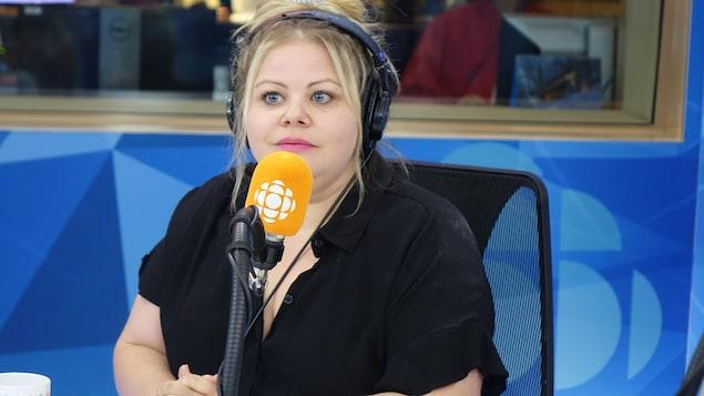 Une femme blonde vêtue de noir parle devant un micro orange.