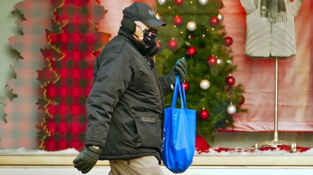 Un homme, un sac de magasinage à la main, porte un masque à l'extérieur pendant la pandémie de COVID-19 en hiver.
