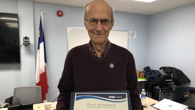 George Cottreau tient fièrement son certificat.