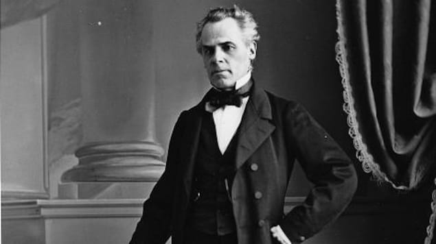 Photo en noir et blanc d'un homme du 19e siècle prenant la pose.