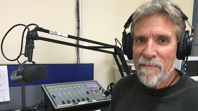 Le journaliste gaspésien Gilles Gagné, chroniqueur à l'émission Au coeur du monde, devant le micro du studio de Radio-Canada à Carleton-sur-Mer.