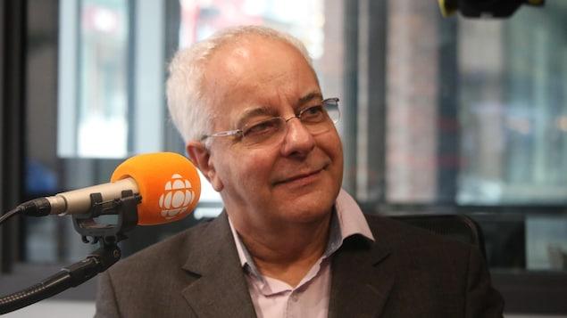 Un homme portant un veston une chemise et des lunettes est au micro de l'émission C'est encore mieux l'après-midi.