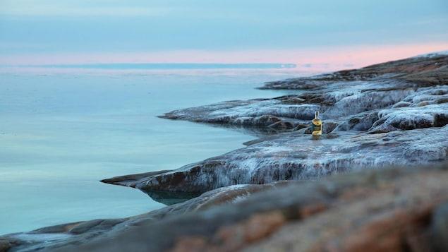 Une bouteille du nouveau gin vieilli sur des rochers, sur le bord de l'eau, de la Distillerie Vent du Nord, sur la Côte-Nord.
