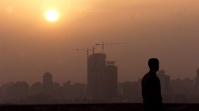 Le smog domine une ville au coucher du soleil. En contre-jour se trouve un homme en avant-plan.