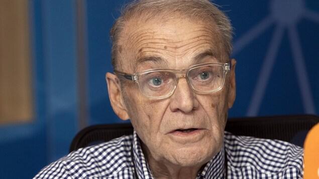 Un homme portant des lunettes parle devant un micro orange.