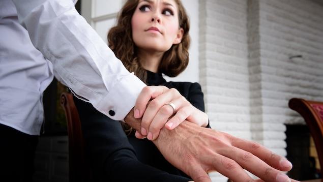 Un femme repousse la main d'un homme.