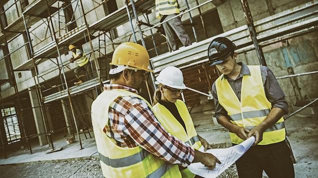 Une femme consulte un document sur un chantier de construction.