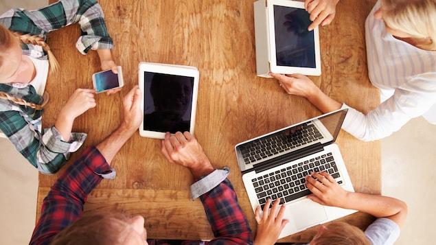 Une famille utilise divers outils électroniques.