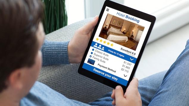 Un homme effectue la réservation d'une chambre d'hôtel sur une tablette électronique.