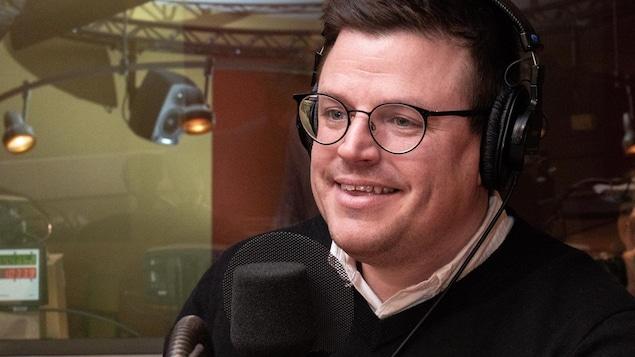 Portant des lunettes, le créateur culinaire sourit à l'animateur.