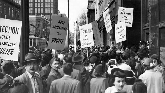 Photo en noir et blanc montrant un foule d'hommes et de femmes tenant des pancartes.
